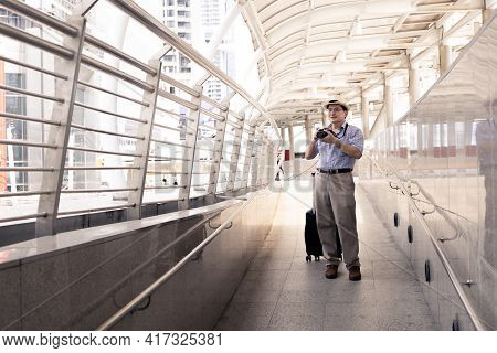 Senior Asian Man Carrying A Camera And Dragging Luggage In The Airport To Prepare To Travel Abroad.