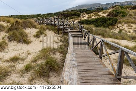 Wooden Walkway Over Grass Covered Sand Dunes To The Beach Of Cala Mesquida, Mallorca