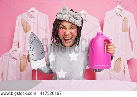 Funny Dark Skinned Positive Afro American Woman Dressed In Nightwear And Blindfold Holds Steam Elect