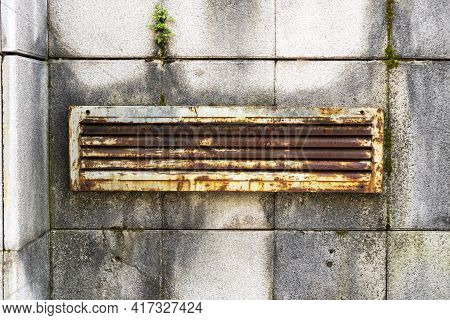 Rusty Iron Ventilation Grill On A Dilapidated Wall With Rotten Overgrown Tiles