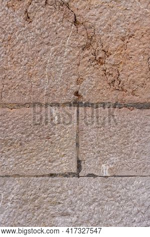 Old Brown Stone Wall With Cracks And Seams