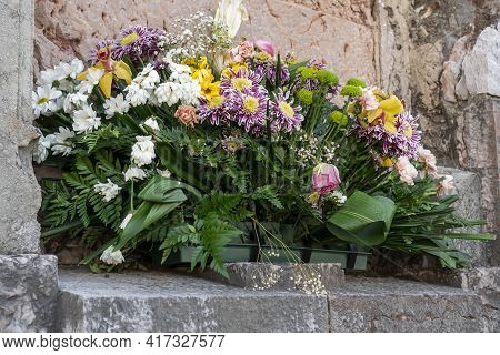 Flowers In A Stone Frame On An Ancient Wall