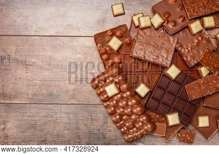 Top View Of Pieces Of Chocolate Bar With Chocolate Chips On Rustic Wooden Table Background. Chocolat