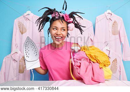 House Chores Concept. Happy Dark Skinned Girl Has Dreadlocks Haircut Smeared Lipstick Does Laundry I