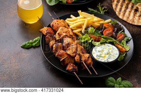 Chicken Fillet Souvlaki, Kebabs On Skewers With Potato Chips, Salad And Fresh Home Made Tzatziki