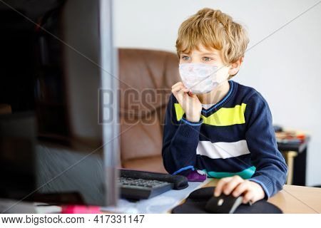 Little Kid Boy With Medical Mask Learning On Computer Notebook. Happy Healthy Child Searching Inform