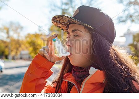 Chronic Disease. Close Up Portrait Of A Teenage Girl Using An Inhaler On The Street, Having An Asthm