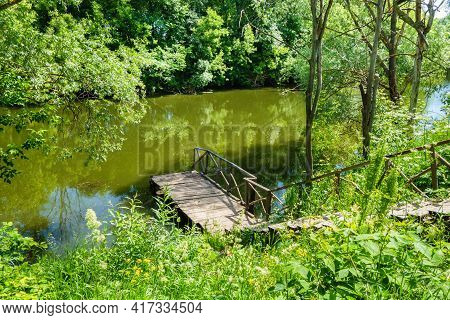 Wooden Staircase Descending To Quiet River Or Lake. Surrounding Landscape Filled With Flowering Plan