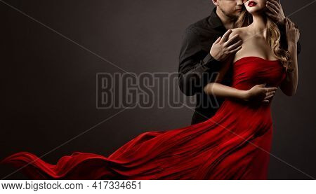 Romantic Lovers Couple Dancing. Man Hugging And Kissing Beautiful Woman In Silk Red Flying Dress. Fa