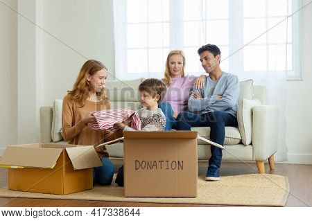 Happy Family Parents Watched Their Daughter And Son Pick Up Waste Items And Clothes And Put Them In