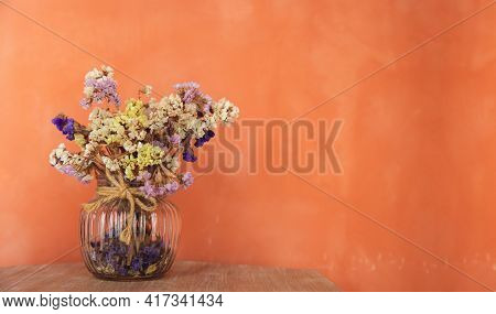 Dried Statice Flowers In Glass Vase By The Orange Loft Wall. Summer Color Tone. Decorative A House B