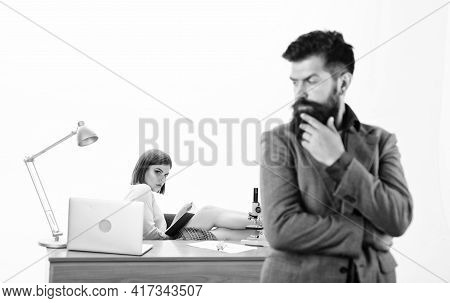 Office Collective Concept. Manager Boss Stand In Front Of Girl Busy With Laptop. Office Manager Or S