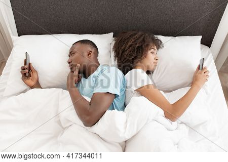 Awake Using Phone For Chat, Couple In Quarrel, Lying On Bed Back To Back, Using Smartphones