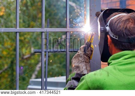 A Bright Flash From An Electrode When A Welder Works To Install A Metal Fence Around A House Against