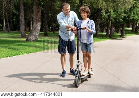 Boy Learning To Ride E-scooter With His Adult Dad
