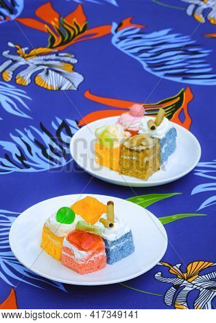 2 Dishes Of Various Mini Cakes On Colorful Tablecloth In Vertical Frame, Focus On Foreground