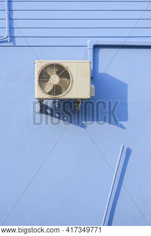 Air Conditioner Compressor With Air Conduit Pipe On Blue Wooden And Concrete Wall Of Vintage House I
