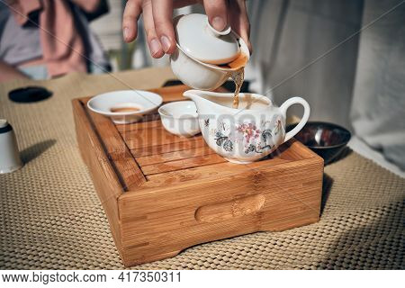 Hands Of Man Brewing Puerh Tea. Man Pours Tea From Gaiwan To Bowl At Tea Tray. Chinese Traditional G