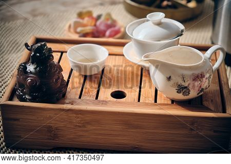 Porcelain Gaiwan, Tea Bowl, Tea Cup And Figurine Of Chinese Dragon Tea God At Bamboo Tea Tray. Gongf