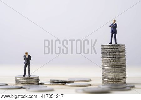 Miniature Rich Man  And Poor Man Standing Standing On Different Height Coins Stacking , Inequality I