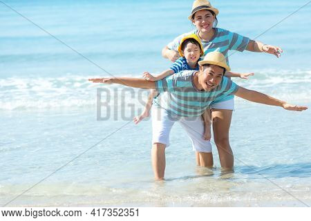 Asia Happy Family Have Fun On The Beach Watching The Landing Planes. Traveling On An Airplane For Le