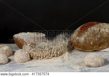 A Bread Loaf Splash On A Pile Of Wholewheat Flour On Marble Countertop With Dark Background. There I