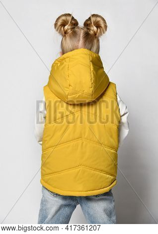 Studio Shot Of Little Girl In Warm Outwear Yellow Sleeveless Vest With Hood, Jeans And Sweatshirt St