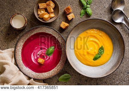 Vegetarian Beetroot And Pumpkin Cream Soups In A Bowls With Croutons On A Brown Concrete Background,