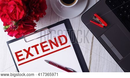The Word Extend Is Written In Red On A White Notepad Near A Laptop, Coffee, Red Roses And A Pen.