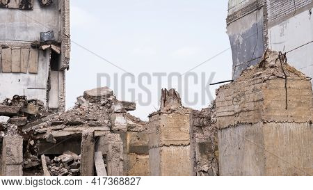 The Remains Of A Ruined Building With Large Foundation Piles In The Foreground. Background