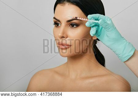 Botulinum Toxin Injections Near A Womans Forehead For Blocking Mimic Wrinkles And Wrinkles Removal.