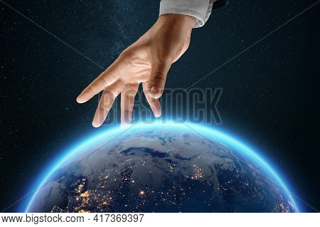 A Businessman's Hand Reaches For The Image Of The Earth From Space. Globalization Concept, Business