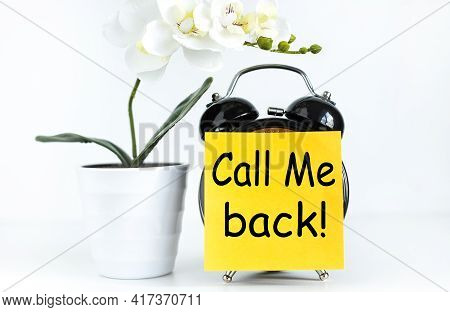Call Me Back. Text On Yellow Sticker Prekpelen Alarm Clock Near Green Orchid Plant On White Backgrou