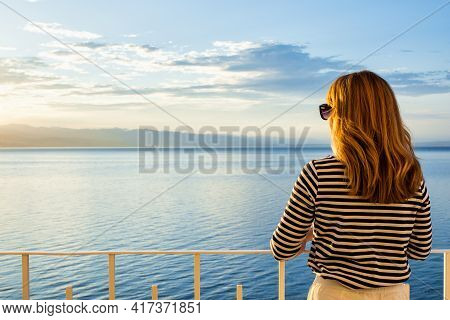 Shot Of Pretty Woman Wearing Striped Sweater And Straw Hat While Standing On Balcony And Looking At