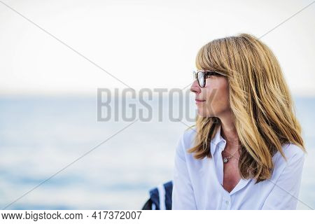 Portrait Of Beautiful Mature Woman Daydreaming While Sitting On A Chair Background With The Sea.