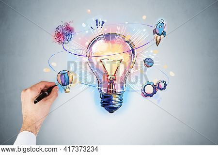 Businessman Hand Drawing Colorful Light Bulb As A Concept Of New Idea For Start Up. Concept Of Creat