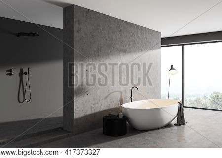 Grey Bathroom Interior With White Tub And Towel, Side View With Concrete Floor And Minimalist Shower