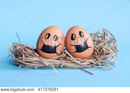 Egg Couple In Protective Masks In Nest Isolated On Blue Empty Space Background. Covid-19 Danger. Con