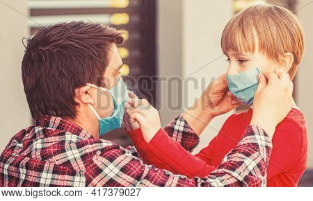 Father Puts A Medical Mask On Her Son. Coronavirus, Illness, Infection, Quarantine, Medical Mask, Co