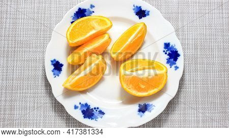 Sliced Slices Of Ripe Orange On A Plate. Top View.