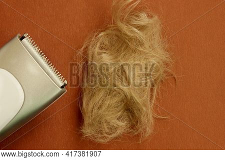 Haircut Machine Is Insulated On A Brown Background, Next To A Strand Of Trimmed Hair. Hair. A Hairdr