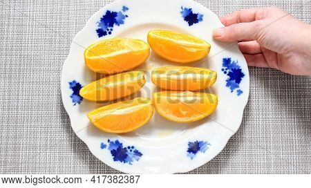 A Hand Picks Up A Plate Of Sliced Ripe Orange Slices. Top View.