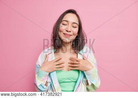 Tender Cheerful Asian Woman Keeps Eyes Closed Hands On Chest Recalls Nice Memories Smiles Tenderly P