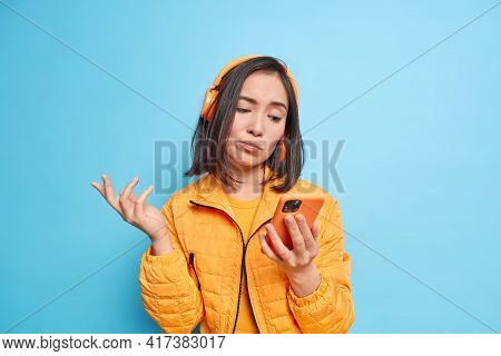 Studio Shot Of Puzzled Hesitant Asian Woman Looks At Smartphone Display Cannot Choose Song To Listen