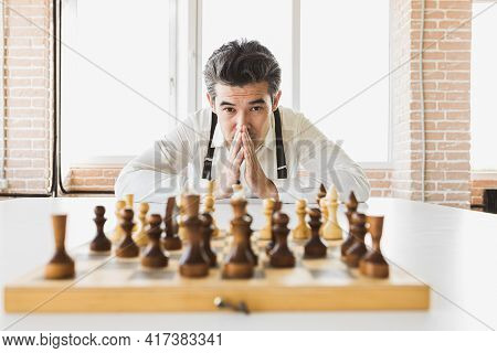 Planning Strategy With Chess Figures On An Old Wooden Table. Businessman Holding And Throwing Chess