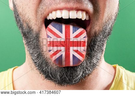 Native Speaker. The Protruding Tongue Of A Bearded Man Is Close-up, In The Colors Of The English Fla