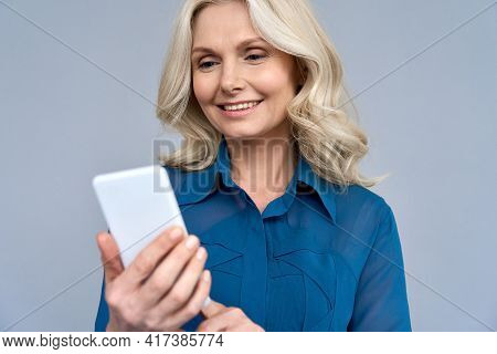 Happy Smiling Mature 50 Years Age Blonde Woman Manager Looking At Cellphone Using Online Mobile Smar