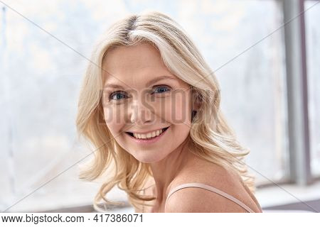 Happy Mature Elder 50s Woman Indoors. Closeup Headshot Portrait Of Attractive Mid Age Woman Looking