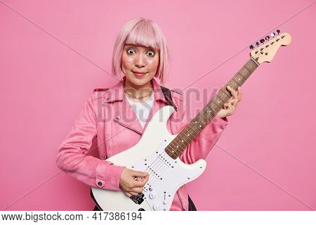Surprised Asian Female Singer With Pink Hair Plays Electric Guitar Being Part Of Popular Band Talent