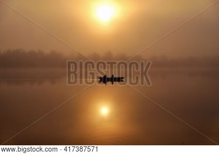 Morning. River, Silhouette Of A Boat And Fishermen, Beautiful Sunlight, Reflection In The Water Of T